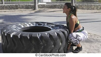 Woman trying to lift the tire - Side view of young fit woman...