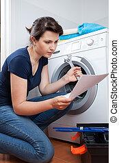 Woman trying to repair washing machine - Woman reading...
