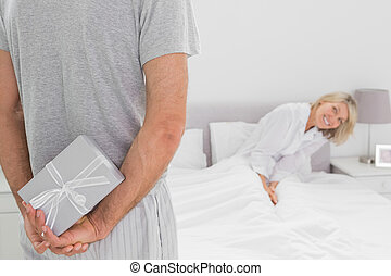 Woman trying to see gift behind par - Woman sitting in bed...