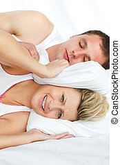 Woman trying to sleep with man snoring - Couple in bed....