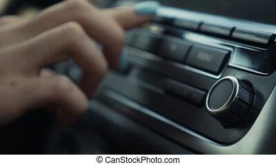 Woman tuning radio volume in car.