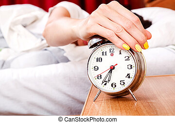 Woman turning off her alarm clock in her bedroom