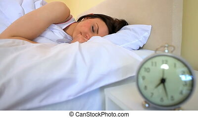 Woman turning off her alarm clock - Young woman turning off...