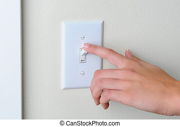 Woman turning off light switch - Womans hand with finger on...