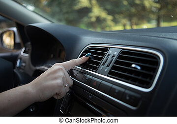 Woman turning on car air conditioning system
