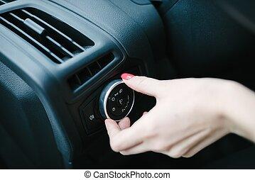Woman turning on car headlights.
