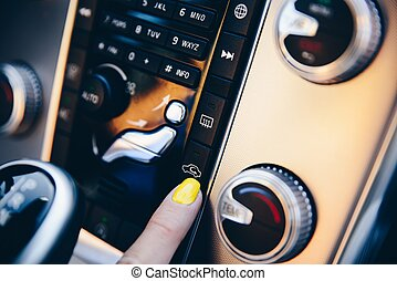 Woman turning on car inner circulation.