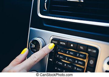 Woman turning on car navigation system.