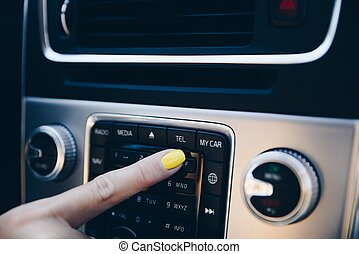 Woman turning on car phone