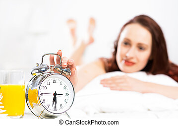 woman turns off the alarm and wake up smiling and happy