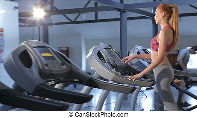 Woman turns on the treadmill at the fitness centre