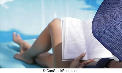 Woman turns the page of book near the swimming pool
