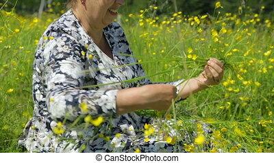 Woman twining a wreath on meadow