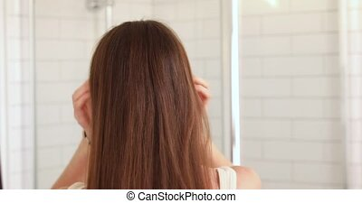 Woman tying her long smooth hair in ponytail, making hairdo,...