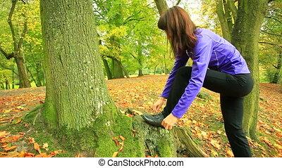 Woman tying running shoes.