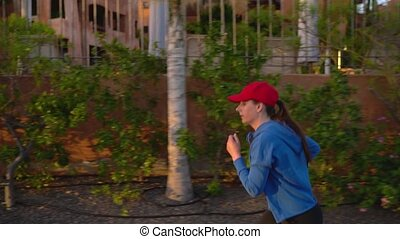 Woman tying shoelaces and starts jogging along the street...
