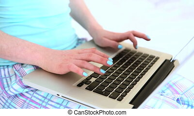 Woman typing on her laptop in bed