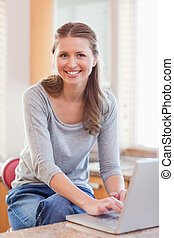 Woman typing on her laptop in the kitchen