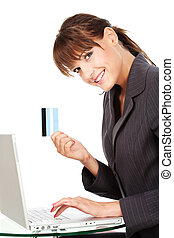 Woman typing on keyboard and holding credit card