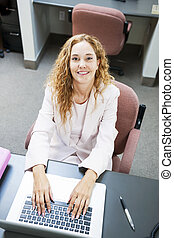 Woman typing on laptop computer at work