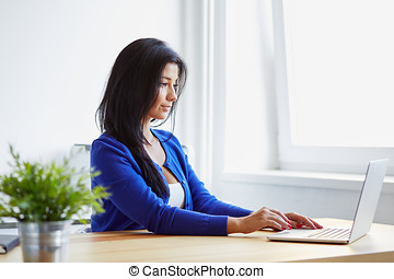 Woman typing on laptop in the office