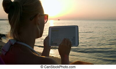 Woman typing on pad sitting by sea at sunset