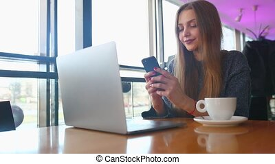 Woman typing text message on smart phone in a cafe. Young woman sitting at a table with a coffee using mobile phone. With blank copy space scree for your advertising text message or promotional content Toned image. Selective focus.