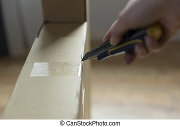 Woman unboxing cardboard box of new furniture with knife