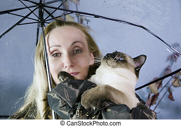 Woman under a transparent umbrella with raindrops holds a cat