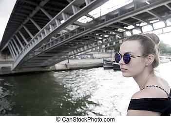 Woman under bridge in Paris, France