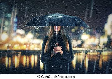 Woman under rain with black umbrella