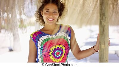 Woman under thatch beach umbrella - Beautiful smiling woman...