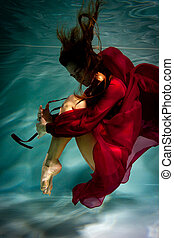 Woman under the water in a red dress.