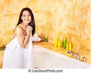 Woman undressing in bathroom