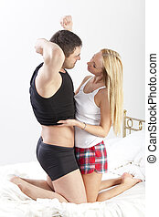 Woman undressing man in bed