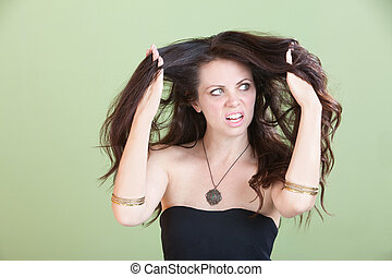 Unhappy Caucasian lady with knotty hair over green background