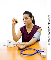 woman unhappy with blood pressure test - Young adult woman...