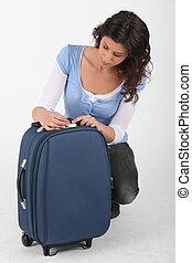 Woman unlocking a suitcase