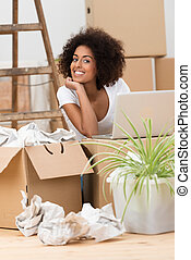 Woman unpacking boxes in her new home - Attractive African...