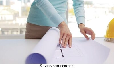 woman unwrapping architectural blueprint