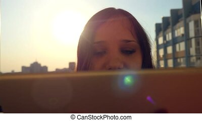 Woman use a tablet in the city at silhouette of blurred sunset