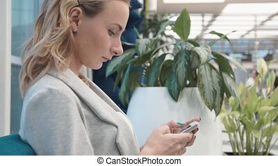 Woman use of mobile phone in shopping mall.