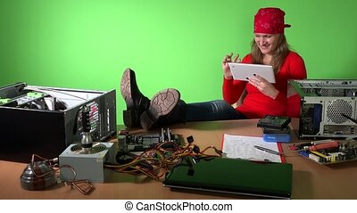young woman use tablet in repair of computer cabinet. there are many computer devices on the table. 4K
