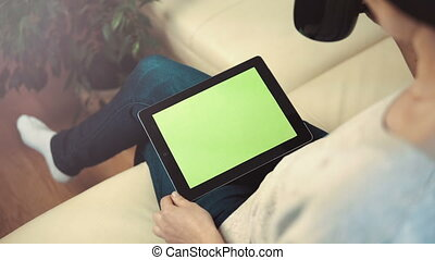 Woman Use Tablet Pc Sitting on Sofa - Indoor shot of a woman...