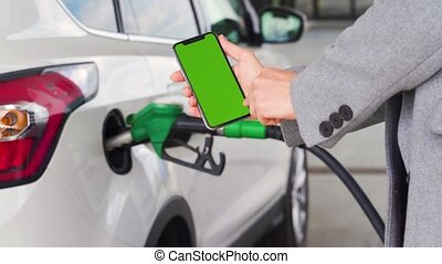 Woman using a mobile application in a smartphone to pay for refueling a car. Smartphone with a green screen. Chroma key