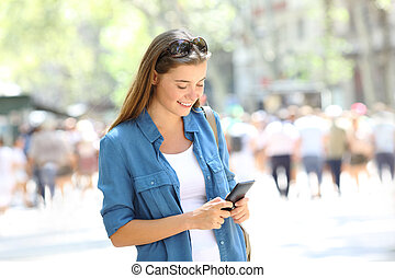 Woman uses a smart phone in the street
