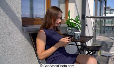 Woman uses a smartphone while while drinking morning coffee on the balcony
