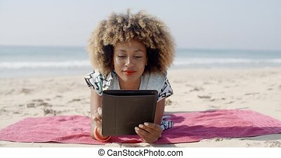 Woman Uses A Tablet On The Beach
