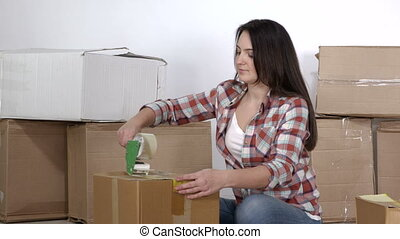 Woman uses adhesive tape dispenser packing cardboard boxes for moving
