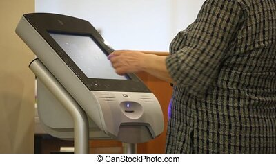 woman uses computer terminal with touchscreen, take coupon...